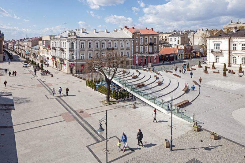 Na zdjęciu widoczny jest Plac Konstytucji 3-go maja w Radomiu, piękna pogoda, na placu są ludzie